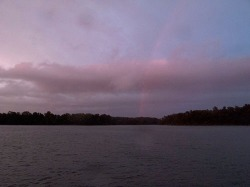 Rainbow over Westerhouse Creek with drowned bunker bobbing in the tide. Raindrops dab the photograph.